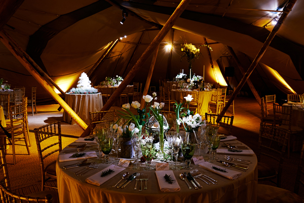 Lighting to wedding cake and tables in tipi
